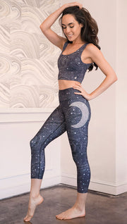 Left side view of model wearing mosaic printed capri leggings with moon artwork on left hip