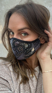 Left side view of model wearing a purple and grey mask with a large moth and the WERKSHOP logo in white on the bottom corner
