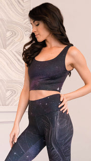 closeup left side view of model wearing reversible tank top with dark purple galaxy night sky on one side and textured black reverse side