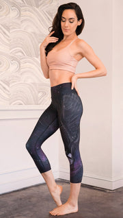 left side view of model wearing fantasy flying pegasus themed printed capri leggings