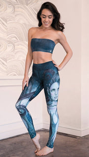 left side view of model wearing full length leggings with mermaid and tentacles printed design