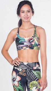 closeup front view of model wearing tropical flower inspired printed sports bra
