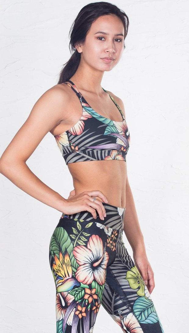 closeup right side view of model wearing tropical flower inspired printed sports bra