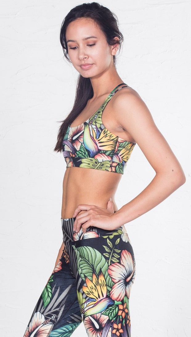 closeup left side view of model wearing tropical flower inspired printed sports bra