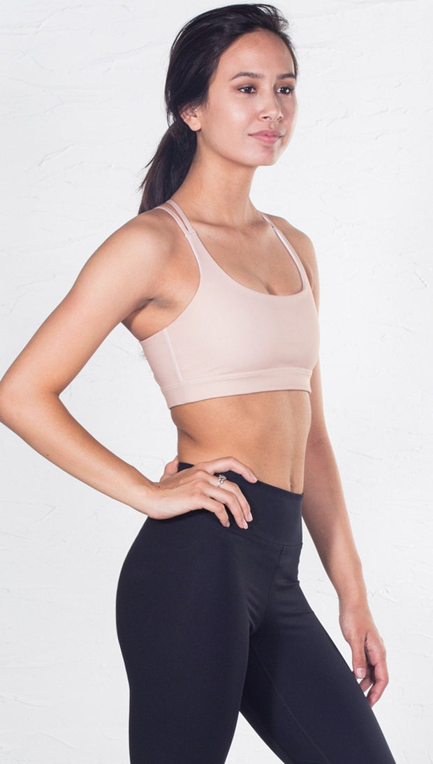 right side view of model wearing nude/beige sports bra
