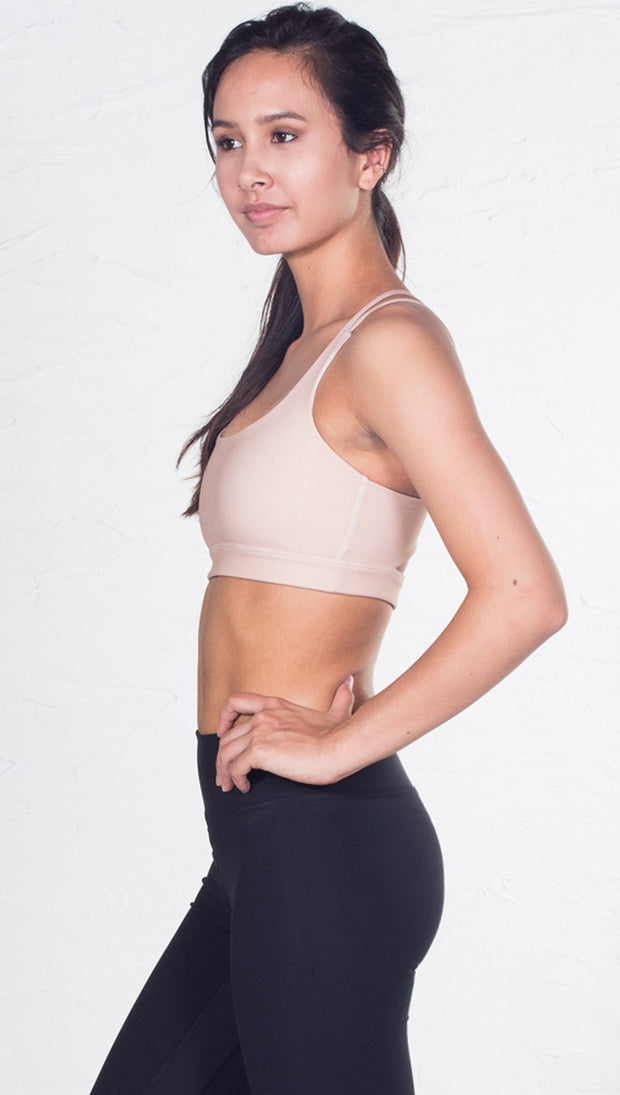 left side view of model wearing nude/beige sports bra