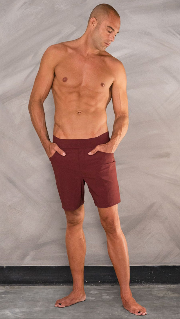 Front view of model wearing men's oxblood performance shorts with slim fit.