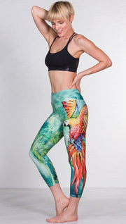 left side view of model wearing macaw themed capri leggings