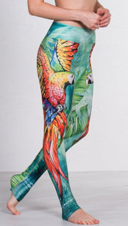 closeup right side view of model wearing macaw themed full length leggings