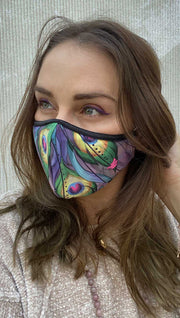 Left side view of model wearing a purple mask with two large green peacock feathers and the WERKSHOP logo in pink on the bottom corner