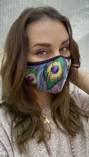 Right side view of model wearing a purple mask with two large green peacock feathers