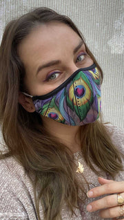 Slightly tilted right side view of model wearing a purple mask with two large green peacock feathers