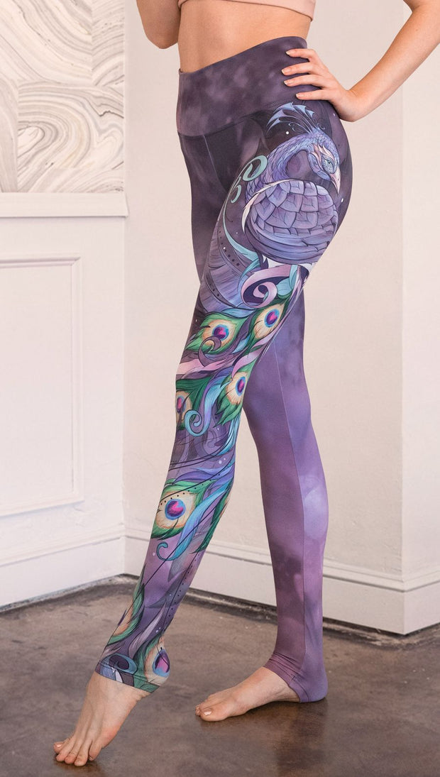 closeup left side view of model wearing peacock themed full length leggings