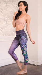 left side view of model wearing peacock themed capri leggings