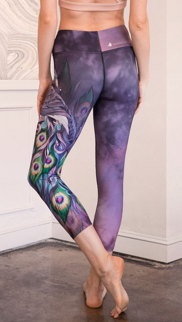 back view of model wearing peacock themed capri leggings