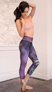 right side view of model wearing peacock themed capri leggings