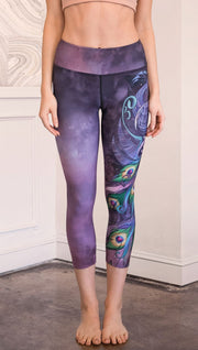 front view of model wearing peacock themed capri leggings
