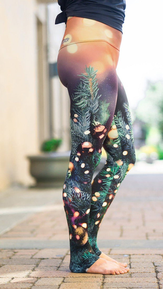 close up right side view of model wearing holiday themed printed full length leggings