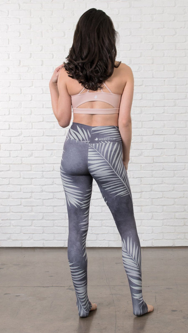 back view of model wearing tropical palm front printed full length leggings