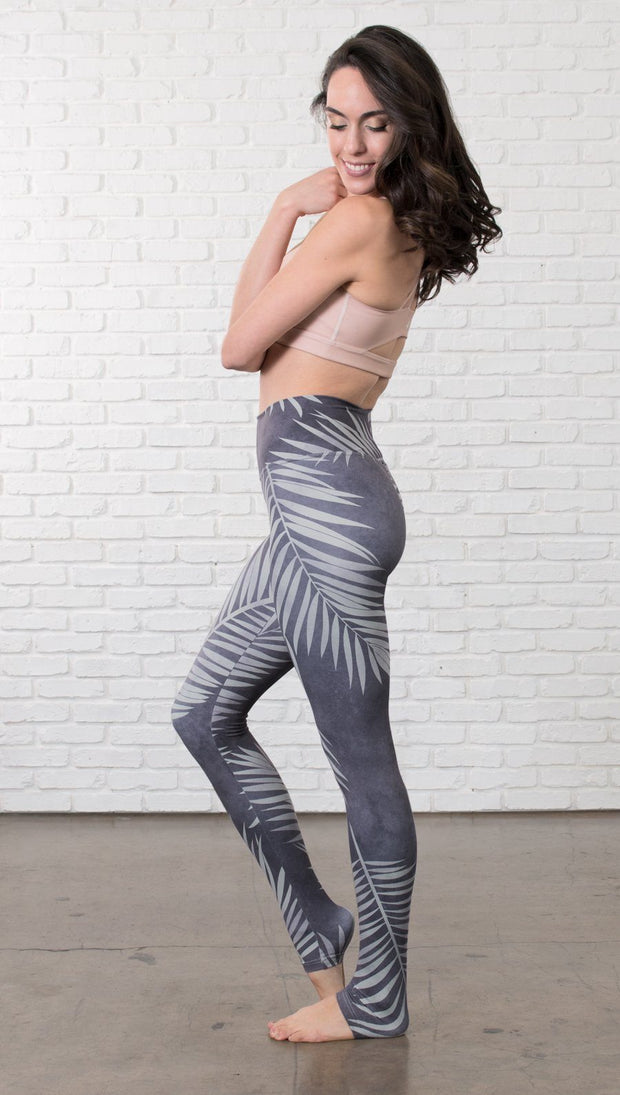 left side view of model wearing tropical palm front printed full length leggings