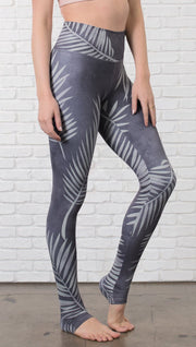closeup right side view of model wearing tropical palm front printed full length leggings