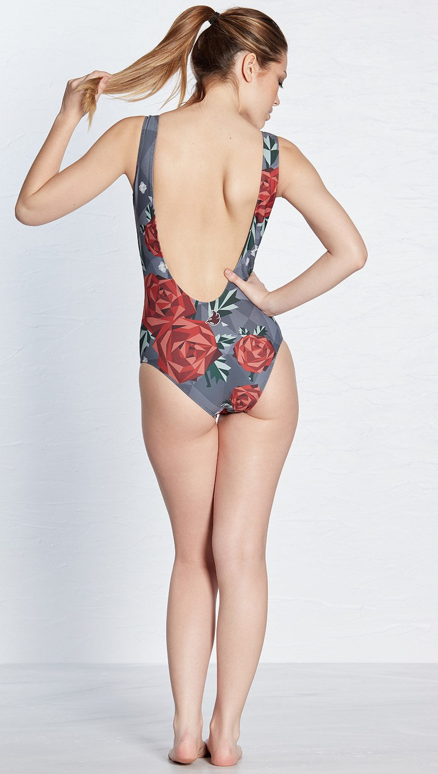 closeup front view of model wearing geometric rose themed one piece swimsuit / leotard