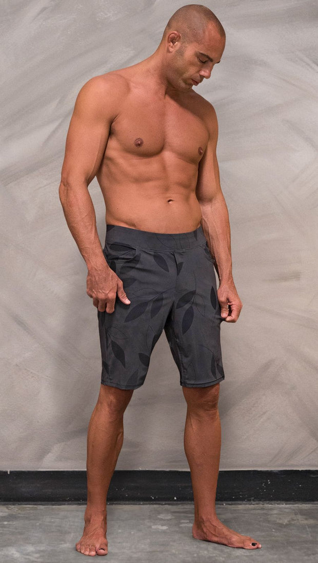 front view of model wearing gray printed performance shorts with slim fit and vilva leaf inspired art