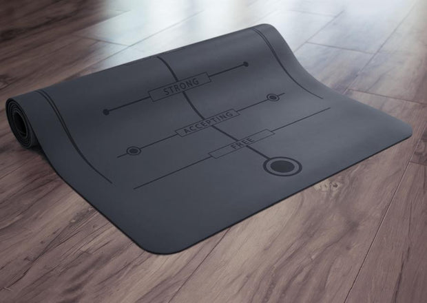 Partially rolled black yoga mat on floor