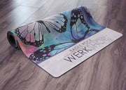 closeup view of partially rolled colorful butterfly themed printed yoga mat