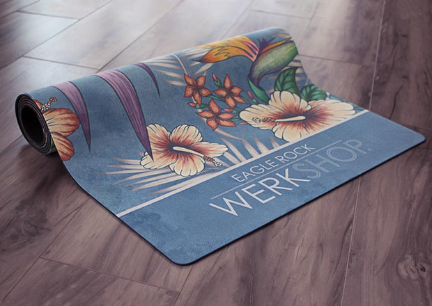 view of partially rolled yoga mat with tropical floral design and blue background