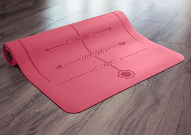 Partially rolled pink yoga mat on floor