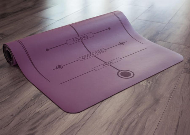 Partially rolled purple yoga mat on floor