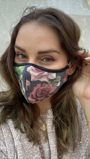 Slightly turned left side view of model wearing a grey mask with pink roses and green leaves and the WERKSHOP logo on the bottom corner in white