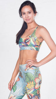 left side view of model wearing tropical flower inspired printed sports bra