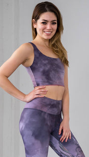 right side view of model wearing watercolor inspired reversible tank top with purple on one side and mauve/pink on the other side