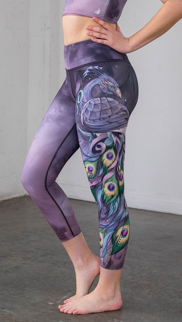 closeup left side view of model wearing peacock themed capri leggings