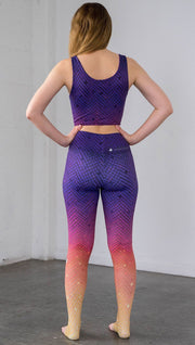 Rear view of a model wearing purple/pink/yellow ombre mosaic tile print full length leggings