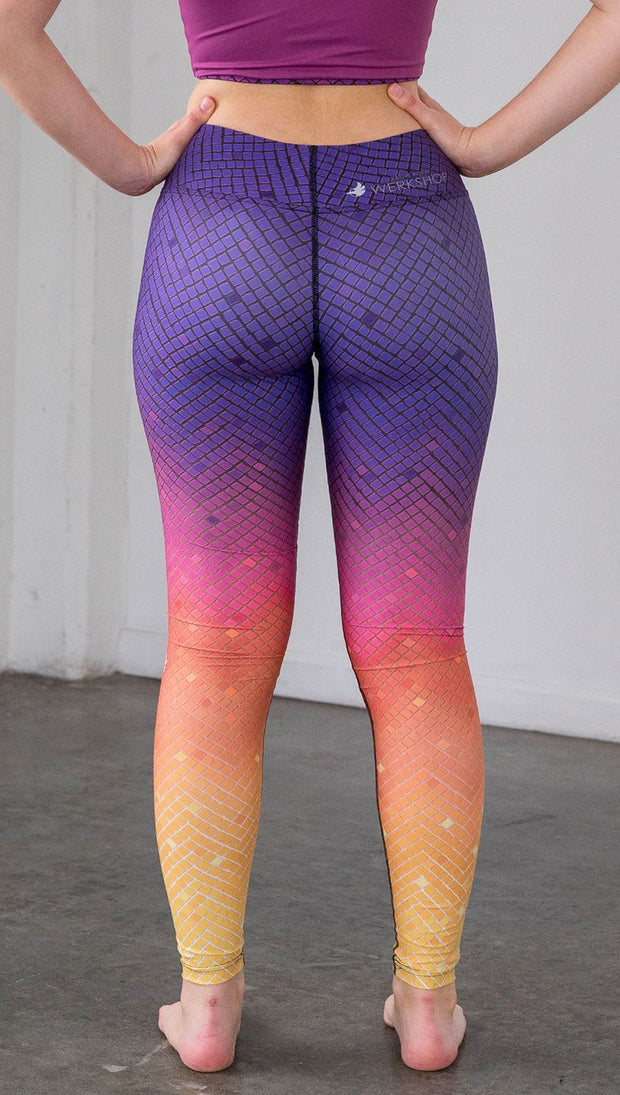 close up rear view of a model wearing purple/pink/yellow ombre mosaic tile print full length leggings