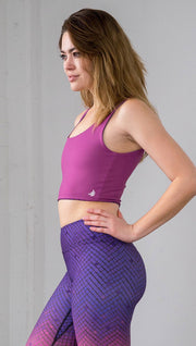 Three quarter length left view of model wearing a fuschia reversible crop top with a purple mosaic tile print on the other side