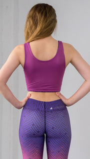 Three quarter length rear view of model wearing a fuschia reversible crop top with a purple mosaic tile print on the other side