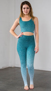 Full length front view of a model wearing teal ombre mosaic tile print leggings with matching top