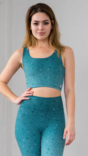 Three quarter length front view of model wearing a teal mosaic tile print reversible crop top with solid teal on the other side