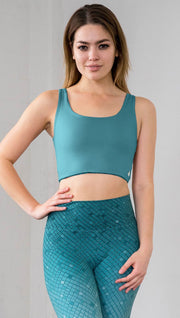 Three quarter length front view of model wearing a teal reversible crop top with a teal mosaic tile print on the other side