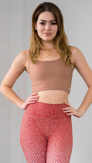 Three quarter length front view of model wearing a reversible light brown/medium skin tone crop top with a beige/lighter skin top on the inside
