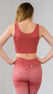 Three quarter length rear view of model wearing a solid coral reversible crop top with coral mosaic tile print on the other side and matching leggings