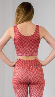 Three quarter length front view of model wearing a coral mosaic tile print reversible crop top with solid coral on the other side and matching leggings