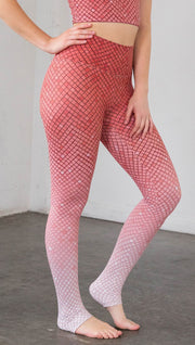 Close up front view of a model wearing coral ombre mosaic tile print leggings with a matching top
