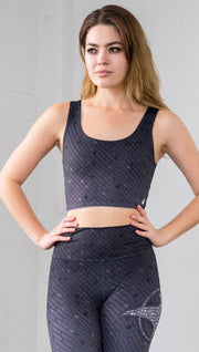 Three quarter length front view of a model wearing a dark gray mosaic tile print reversible crop top with blue mosaic tile print on the other side