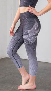 Close up left side view of mosaic printed capri leggings with eagle artwork on left hip