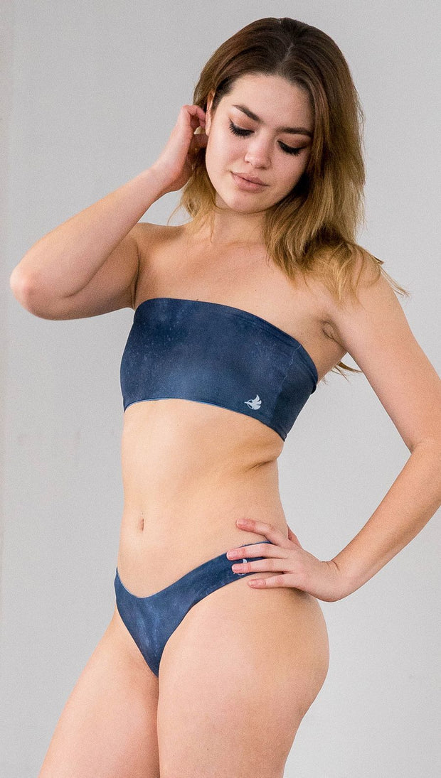 Closeup left side view of model wearing reversible bikini bottom with ethereal dark blue water print on one side and textured watercolor print on the reverse side